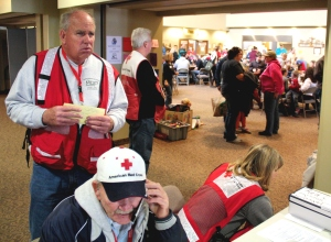 Dave Stoner waits for a group of people to enter the American Red Cross shelter in Washington, Ill., while Walt Lockhart coordinates activities on the phone. The two volunteers are overseeing the shelter at the Crossroads United Methodist Church  (American Red Cross photo by Carl Manning)